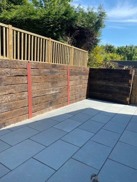 Limestone paving patio with reclaimed oak sleeper wall